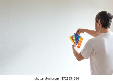 Diseñador o arquitecto escogiendo el color de la pared a partir de la guía de la paleta de colores, muestras de colores en la mano
