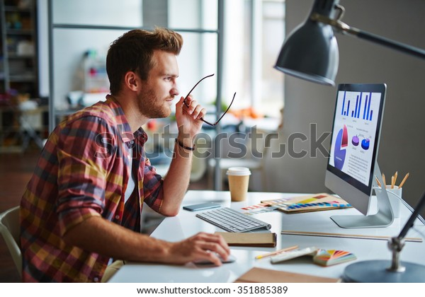 Man as a designer sitting at his table and working on computer