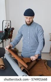 Man designer sorting leather in a workshop