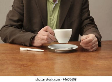 Man at desk drinking coffee