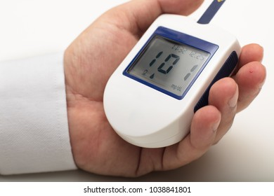 Man with diabetes holding a portable digital glucose meter in his hand as he measures his own blood sugar levels after drawing a drop of blood from his finger. Data at normal blood sugar level