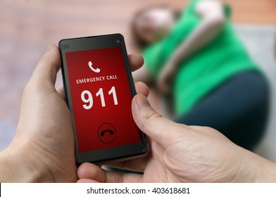 Man dialing emergency (911 number) on smartphone. Injured woman had accident and is lying on the floor.