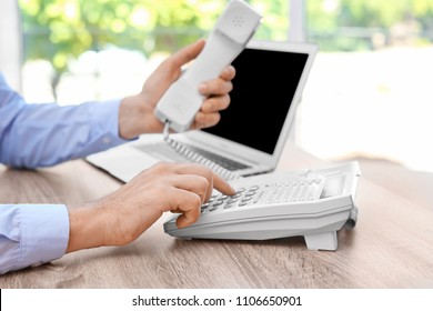 Man dialing number on telephone at workplace