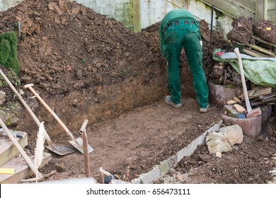 Man with dig of soil on a outdoor construction site.