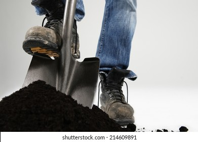 Man digging with foot on shovel applying pressure on white background