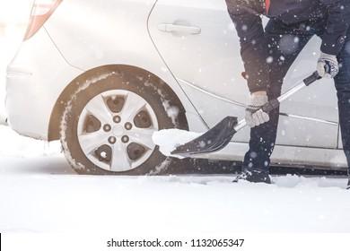 Man digging snow with shovel next to his car.
