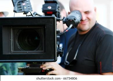 Man with digital cinema camera on movie set.
