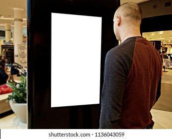 A man with Digital media blank black and white screen modern panel, signboard for advertisement design in a shopping center, gallery. Mockup, mock-up, mock up with blurred background, digital kiosk.