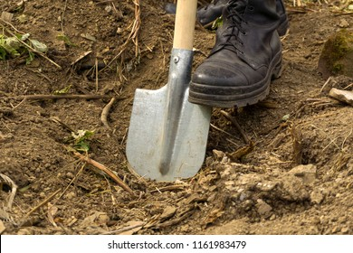 a man digs a dry earth with a spade - close-up of a foot in an army boot, resting on a blade