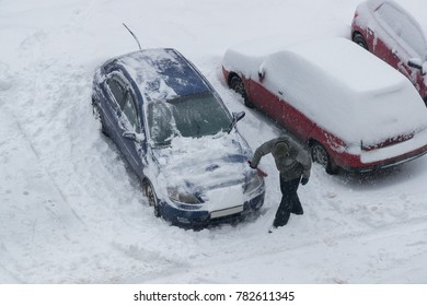 man digs snow from his car in the parking lot