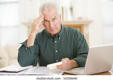 Man in dining room with laptop and paperwork looking frustrated