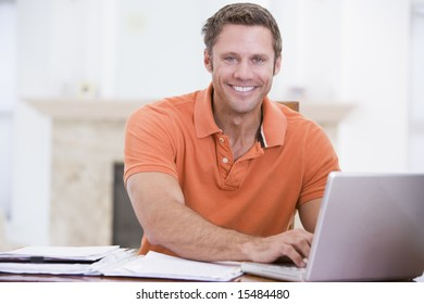 Man in dining room with laptop writing and smiling