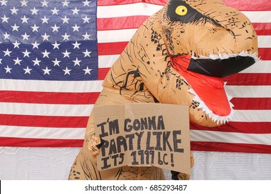 a man in a Dinosaur costume holds a hand written cardboard sign while standing in front of an American flag in a photo booth.