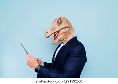 Man with dinosaur mask typing on tablet.Blue background