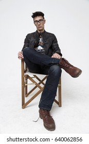 Man in a director's chair on a white background in the studio, a man in a black leather jacket, jeans and glasses. modern film art