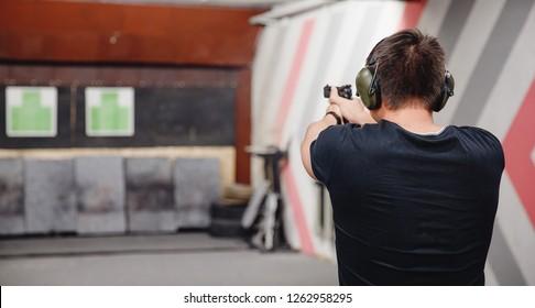 Man directs firearm gun pistol at target firing range or shooting range.