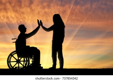 A man disabled in a wheelchair from having fun with each other at sunset. The concept of leisure and support to persons with disabilities