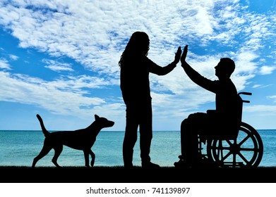 A man disabled in a wheelchair with having fun with friend and dog by the sea. The concept of support and assistance to people with disabilities