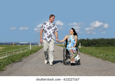 Man and disabled woman walking outdoor hand in hand looking at each other - day light - wheelchair user and her husband