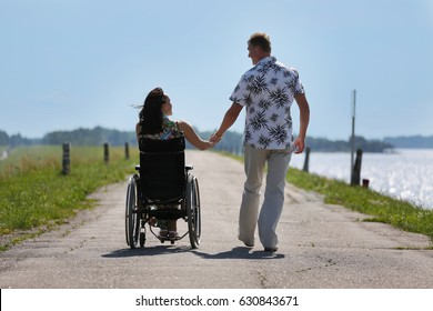 Man and disabled woman walking outdoor hand in hand looking at each other - day light - wheelchair user and her loving husband, view from behind
