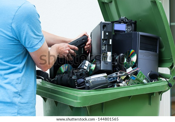 Man discarding old electronics int the plastic bin