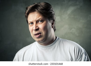 Man with disgusted expression over dark grey background