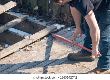 Man Dismantling an Old Wooden Deck with a Red Crowbar in a Backyard - Shutterstock ID 1663542742