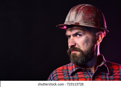 Man with distrustful face on black background, copy space. Builder or miner with thick beard. Worker with brutal image wears dirty helmet and plaid shirt. Construction and hard work concept