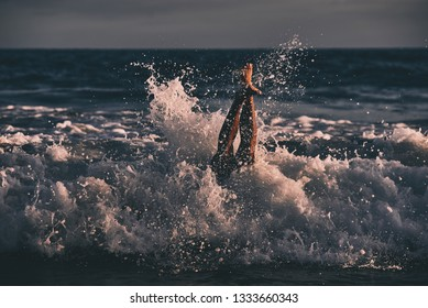 A man dives into the surf at sunset with just his legs protruding.