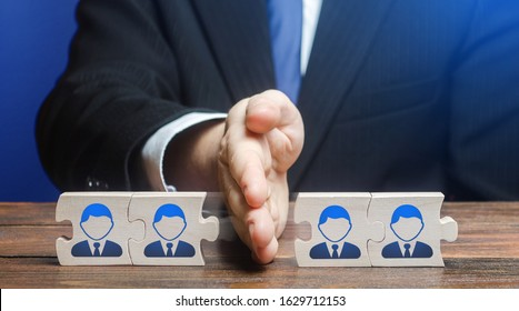 A man divides puzzle team of employees. Team split, structural fragmentation into small units. Improving company efficiency. Staff dismissal reduction. Distribution group members to parallel projects.