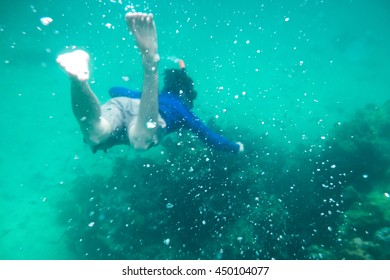 Man diving in emerald andaman sea on coral reef
