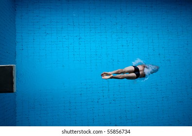 man diving into blue pool water