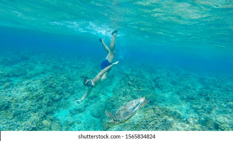 A man in a diving mask and fins diving along a turtle, next to the shore of Gili Air, Lombok Indonesia. Beautiful and crystal clear water. Peaceful coexistence of human and animal. Dream coming true.