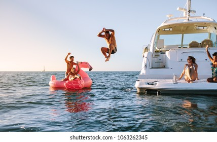 Man diving in the sea with friends sitting on yacht and inflatable toy. Group of friends enjoying a summer day on a inflatable toy and yacht. - Shutterstock ID 1063262345