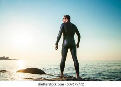 Man in diving suit standing in waves