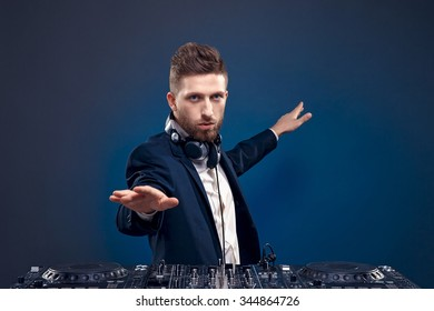 Man DJ in dark suit play music on a Dj's mixer. Studio shot. Dark blue background
