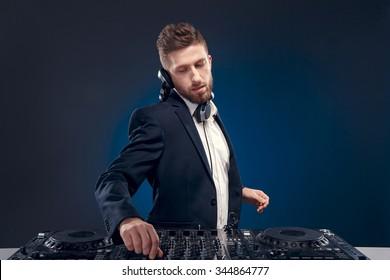 Man DJ in dark suit play music on a Dj's mixer. Studio shot. Dark blue background