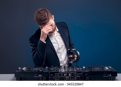 Man DJ in dark suit play music on a Dj's mixer. Studio shot. Dark blue background. Sad of something going wrong.