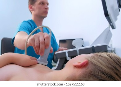 Man doctor making ultrasound diagnostic of mammary glands of young woman on bust. He runs ultrasound sensor over patient's mammary glands and looks at image on screen. Diagnosis of internal organs.