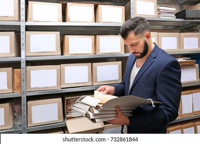 Man with documents in archive