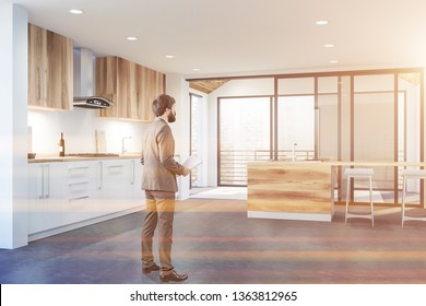 Man with documents standing in modern kitchen interior with wooden countertops, cupboards and bar. Real estate agent work concept. Toned image