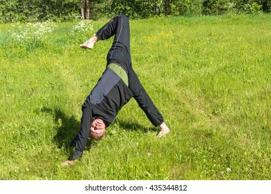 A man does asana on green grass in a Sunny summer day.