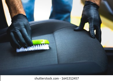 Man does car upholstery cleaning - Professional chemical cleaning with suction method. Hygienic work and stain removal on the vehicle seat.