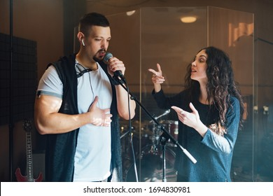 a man does chanting with a teacher in vocal lesson pointing to the correct breathing in the chest