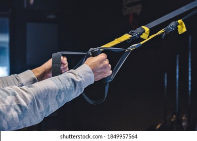 Man Does Crossfit exercise With Trx Fitness Straps In Gym.