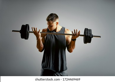 A man does exercises with a barbell on a gray background. The athletic body of a young man in muscle tension makes an approach with a barbell. Copy space