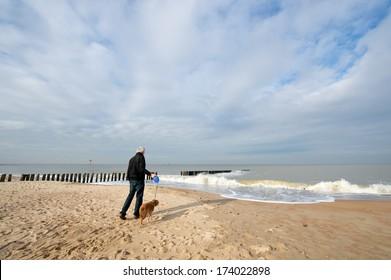 man with dog at the beach in Dutch Zeeland