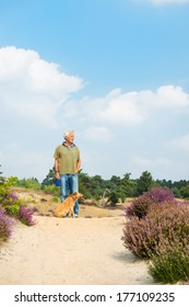 Man with dog in blooming heather landscape