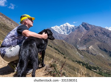 Man with a dog enjoying the beautiful scenery of Himalayan mountains on the way to Everest base camp. Taboche peak and Phortse village seen in the distance.