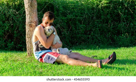 man and a dog hugging in a green park